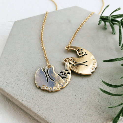 an image of a pendant necklace featuring a mum and baby sloth - one of our sloth related gifts ideas