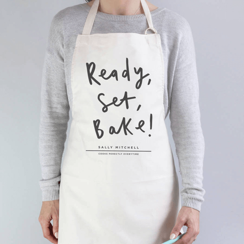 an image of a personalised baking apron which says ready set bake on the front - one of our personalised baking gifts ideas